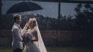 Happy married couple in love talking to each other while standing on a rain with umbrella.