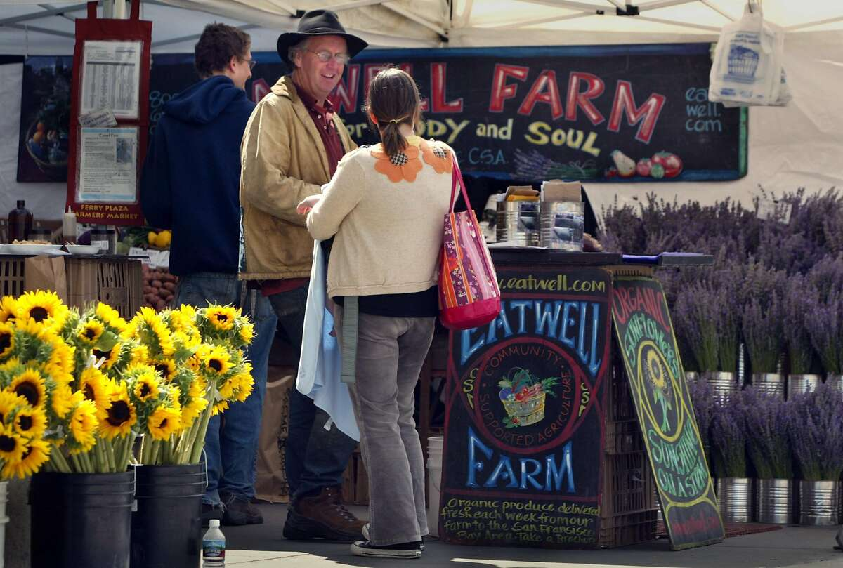 tourism23_002_df Nigel Walker from Eatwell Farm talks with a friend at his stand. The farmer's market at the Ferry Building attracts alot of people from around the Bay area. That is who is being targeted in a new ad campaign by the S.F. Convention and Visitors Bureau designed to draw more tourists to the city. Deanne Fitzmaurice/The Chronicle