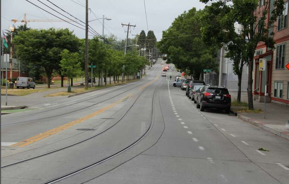 East Yesler Way near 13th and 14th avenues offers a bike lane marked by  dotted lines. However, there is no separation from traffic and cyclists  who wish to pass a stopped bus or other cyclists must merge into the  regular traffic lane where the streetcar tracks are. Photo: Campiche Arnold PLLC