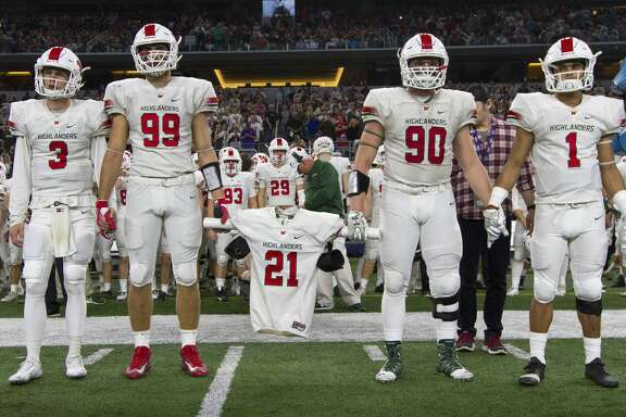The Woodlands football players Michael Purcell, left, and Zachary Loane carry the jersey of linebacker Grant Milton, who was named an honorary captain before a UIL Class 6A Division I state final against Lake Travis at AT&T Stadium Saturday, Dec. 17, 2016, in Arlington. Grant was injured during the teamÕs state playoff game against Austin Bowie on Nov. 26 at McLane Stadium on the campus of Baylor University. After brain surgery and 17 days in a Waco hospital, Grant was transferred to a medical facility in The Woodlands Nov. 13