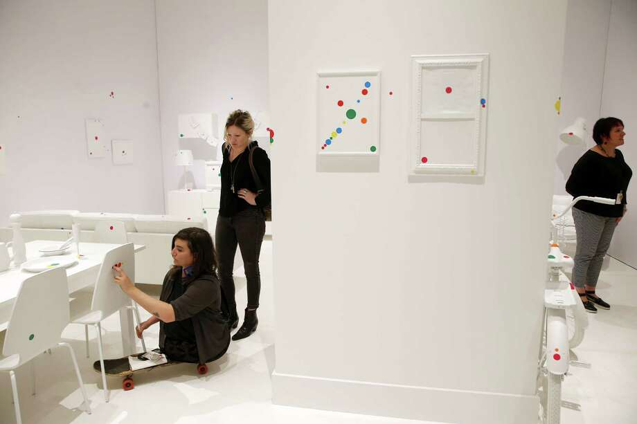 """People stick colored dots to any surface in """"The Obliteration Room"""", an installation at the Yayoi Kusama: Infinity Mirrors exhibit, which is on display June 30 through September 10 at the Seattle Art Museum. Photographed, Wednesday, June 28, 2017. Photo: SEATTLEPI.COM / SEATTLEPI.COM"""