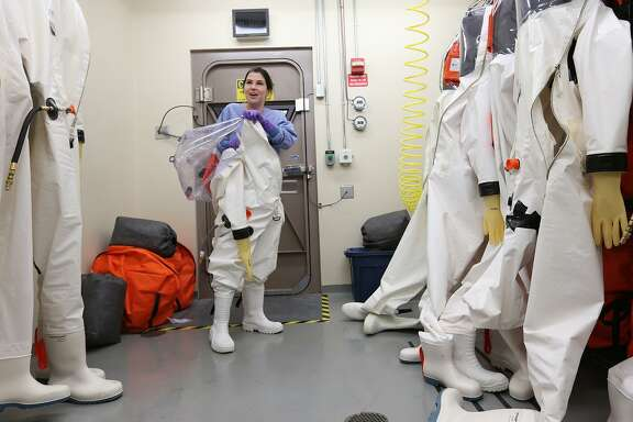 Researcher Dr. Gabi Worwa, DVM, removes her suit after working with the Ebola virus in the biosafety level four lab at the Texas Biomedical Research Institute in this 2014 photo.