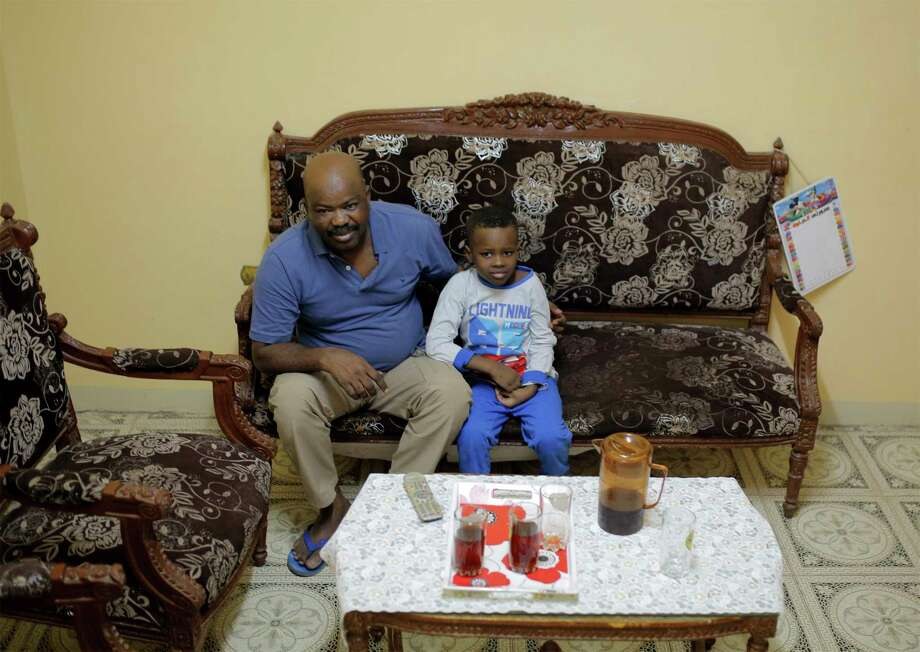 Sudanese activist Tayeb Ibrahim, who had worked to expose Sudanese abuses in the volatile South Kordofan province and hopes to see family living in the U.S. state of Iowa, watches television with his son Mohammed, in Cairo, Egypt, Wednesday, June 28, 2017. Dozens of Sudanese activists living in Egypt as refugees, many of whom fled fundamentalist Islamic militias and were close to approval for resettlement in the United States, now face legal limbo in Egypt after the Supreme Court partially reinstated President Donald Trump's travel ban. (AP Photo/Amr Nabil) Photo: Amr Nabil, STF / Copyright 2017 The Associated Press. All rights reserved.
