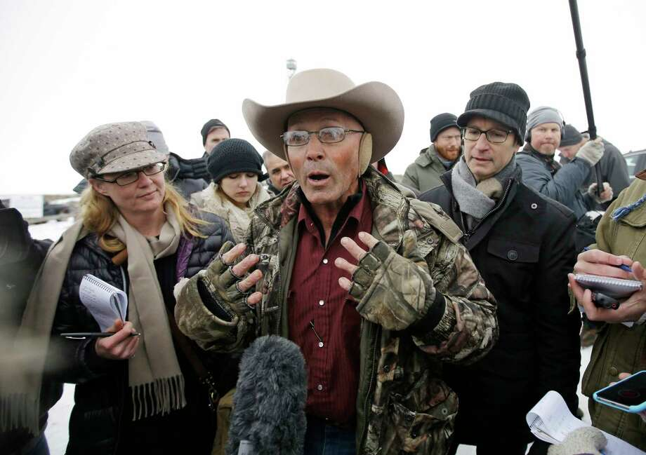 "FILE - In this Jan. 5, 2016 file photo, Robert ""LaVoy"" Finicum, center, a rancher from Arizona, talks to reporters at the Malheur National Wildlife Refuge near Burns, Ore. An FBI agent has been indicted on accusations that he lied about firing at Finicum in 2016 when officers arrested leaders of an armed occupation of a federal wildlife refuge in rural Oregon. Sources familiar with the case say the agent will face allegations of making a false statement with intent to obstruct justice, The Oregonian/OregonLive reported Tuesday, June 27, 2017. (AP Photo/Rick Bowmer, File) Photo: Rick Bowmer, STF / Copyright 2017 The Associated Press. All rights reserved."