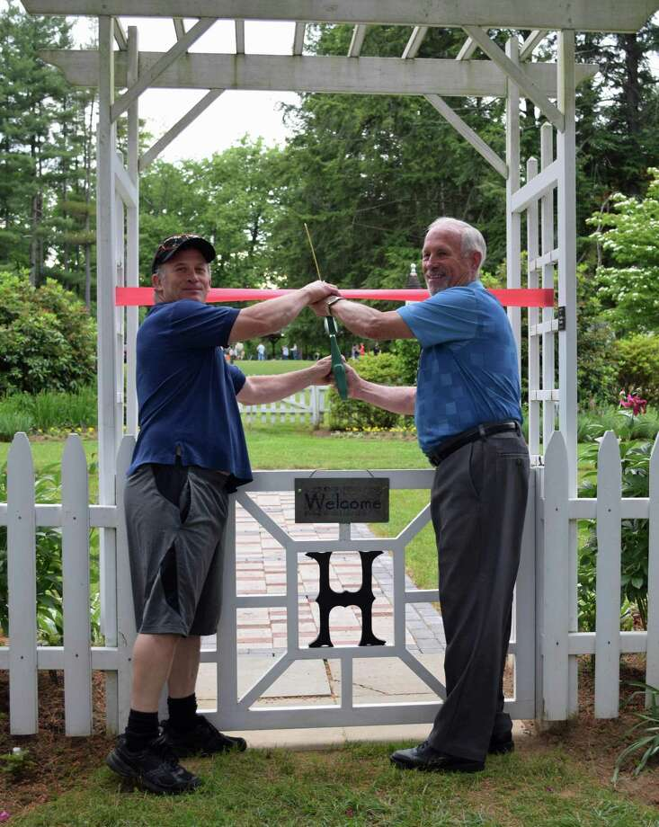 Lee Colville, a member of the Harrybrooke board of managers, right, and his son, Steve, who laid the bricks of a new memorial walkway in the garden at the park with Pete Messer, cut the ribbon at the walkway's recent dedication ceremony. Photo: Deborah Rose / Hearst Connecticut Media / The News-Times  / Spectrum