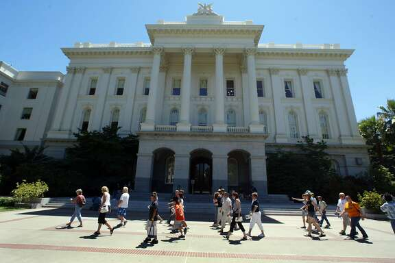 sactobuzz251_cs.jpg Event on 7/19/04 in Sacramento Visitors barve 90-degree-heat as they finish a visit to the California state capitol building.  Since Gov. Arnold Schwarzenegger took office, the leafy, quiet town is less calm than it used to be. Tourists crane their necks to spot him at work. Locals pack his favorite lunch spots to see him eat. Exercisers watch him surreptitiously at the gym. And if he or First Lady Maria Shriver make a scheduled public appearance, hundreds of locals turn out to be a part of the moment, as if it were living history.   Chris Stewart / The Chronicle  Ran on: 08-08-2004 Oscar Warner, who's been guiding Capitol tours for 14 years, holds up a photo of the governor and his wife for his group.  Ran on: 08-08-2004