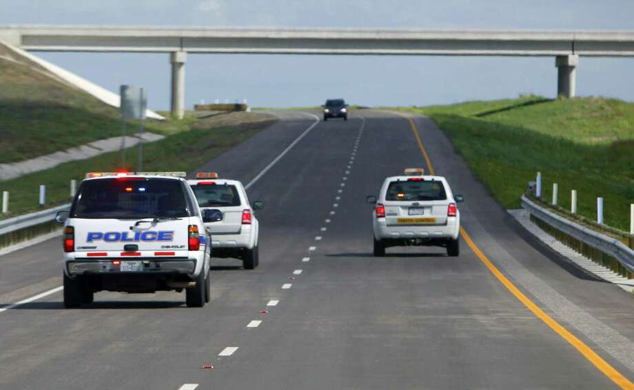 A car is seen on Texas 130 coming towards work crews and police cars before the road officially opened Oct. 24, 2012. Work crews and police officers drove north on the southbound lanes between Seguin and Austin to open the road behind them. The highway came with the highest speed limit — 85 mph — of any road in the country. Photo: William Luther /San Antonio Express-News / © 2012 San Antonio Express-News