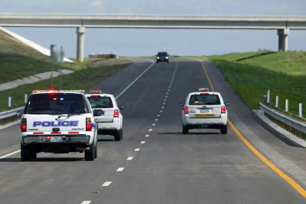 A car is seen on Texas 130 coming towards work crews and police cars before the road officially opened Oct. 24, 2012. Work crews and police officers drove north on the southbound lanes between Seguin and Austin to open the road behind them. The highway came with the highest speed limit — 85 mph — of any road in the country.