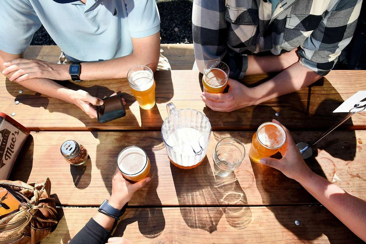 A group of friends enjoy beers at Arthur Mac's Tap and Snack beer garden in Oakland, CA, on Saturday June 24, 2017.