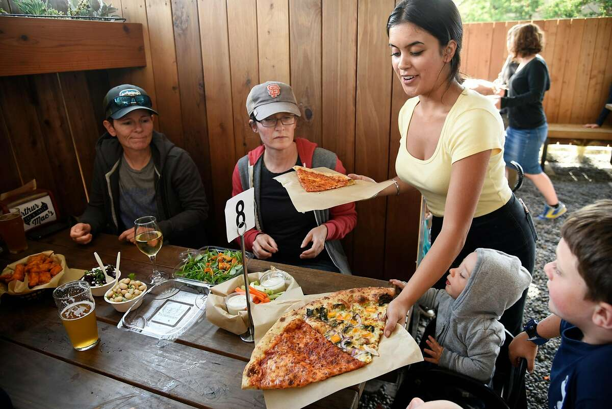 Sever Henna Papineau delivers slices of pizza to Suz Sillett, left, and Tamara Ooms and friends at Arthur Mac's Tap and Snack beer garden in Oakland, CA, on Saturday June 24, 2017.
