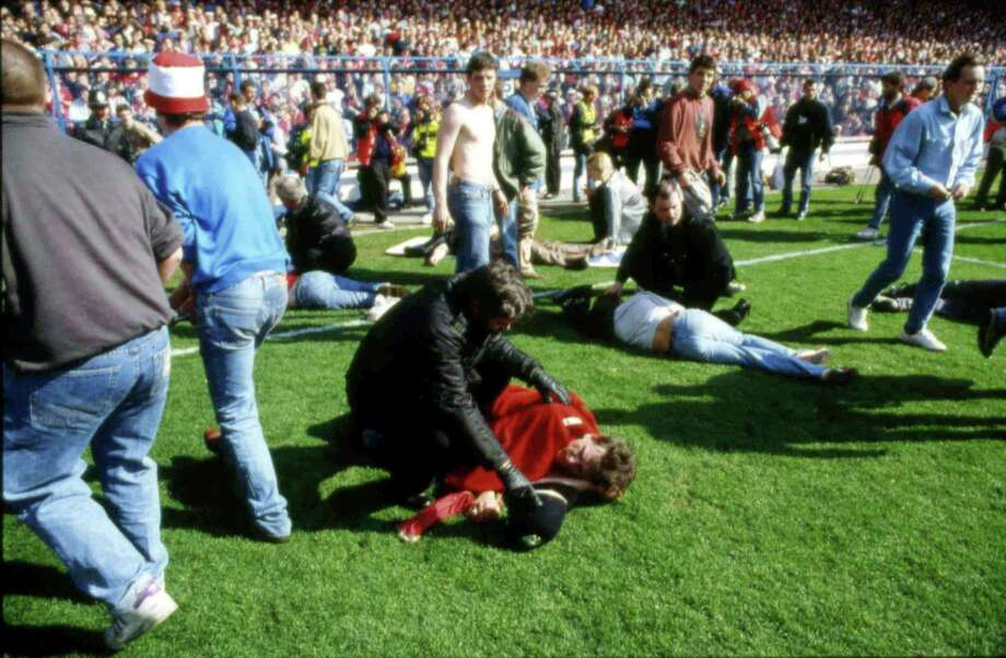 FILE - In this April 15, 1989 file photo, police, stewards and supporters tend and care for wounded supporters on the pitch at Hillsborough Stadium, in Sheffield, England. British prosecutors on Wednesday June 28, 2017, are set to announce whether they plan to lay charges in the deaths of 96 people in the Hillsborough stadium crush _ one of Britain's worst-ever sporting disasters. (AP Photo, File) Photo: STR / AP