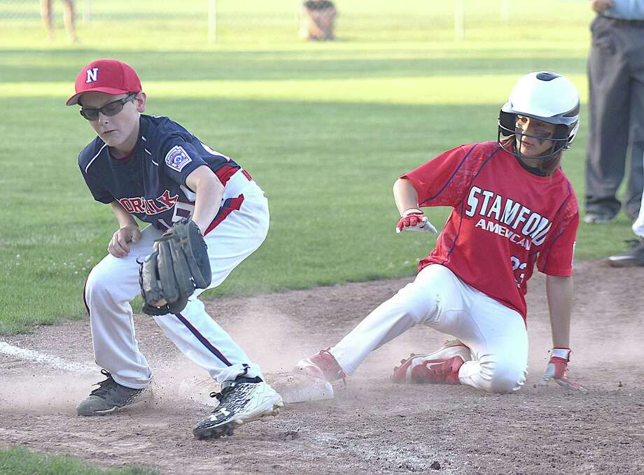 Norwalk third baseman Seamus Herlihy, left, spears the ball out of the air as Stamford American's Charlie Karukas slides safely into third in a District 1 Little League pool play game at Broad River Field in Norwalk. Stamford American won 5-4 in seven innings. Photo: John Nash / Hearst Connecticut Media / Norwalk Hour