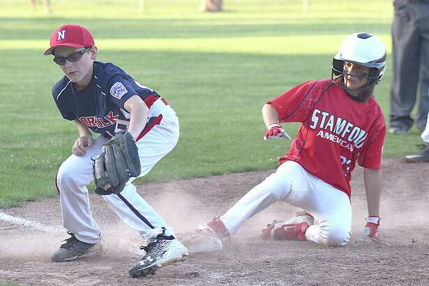 Norwalk third baseman Seamus Herlihy, left, spears the ball out of the air as Stamford American's Charlie Karukas slides safely into third in a District 1 Little League pool play game at Broad River Field in Norwalk. Stamford American won 5-4 in seven innings.