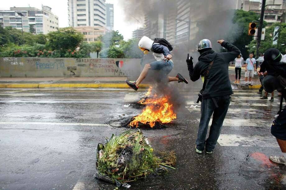 A masked protester jumps over a burning barricade in Caracas, Venezuela on Wednesday as authorities continue their search for a helicopter pilot who  on Tuesday fired on the nation's Supreme Court and Interior Ministry.  Photo: Ariana Cubillos, STF / AP