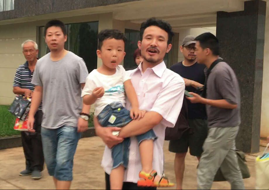 This image from video shows Chinese labor activists Hua Haifeng, center, carrying his son Bobo, and Li Zhao, second from left, leaving a police station. Photo: Gerry Shih, STF / Copyright 2017 The Associated Press. All rights reserved.