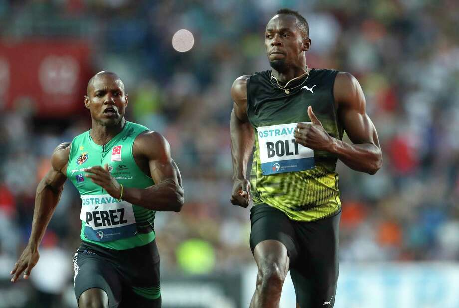 """Usain Bolt, right, beats Cuba's Yunier Perez by three-hundredths of a second (10.06 to 10.09) to win the 100 meters at the Golden Spike meet. """"I'm not happy with the time,"""" Bolt said of one of his tune-ups before taking part in the world championships in August for the final meet of his career. Photo: Petr David Josek, STF / Copyright 2017 The Associated Press. All rights reserved."""