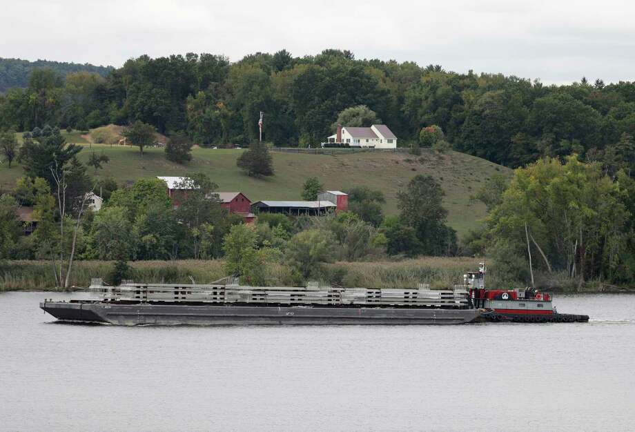 In this Wednesday, Sept. 28, 2016 photo, a tugboat and barge travel south on the Hudson River in Stuyvesant, N.Y. A group of citizens, lawmakers and environmentalists is fighting a proposal to establish more than 40 commercial anchorages at locations along a stretch of the Hudson River running north from New York City. Shipping industry officials said they need safe places to anchor, sometimes for days, barges hauling North Dakota crude oil to East Coast refineries and export terminals. (AP Photo/Mike Groll)  Photo: Mike Groll / Copyright 2016 The Associated Press. All rights reserved.