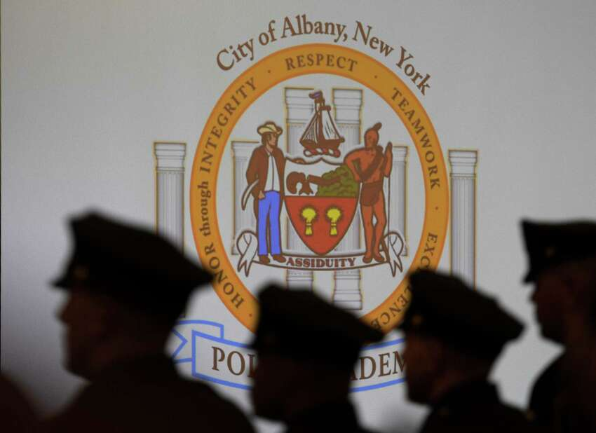 FILE - Albany police officers' silhouettes are seen against the Albany Police Academy flag at the Albany Capital Center April 3, 2017 in Albany, N. Y. (Skip Dickstein/Times Union)