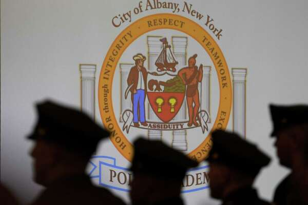 Silhouetted by the Albany Police Academy flag are some of the newest officers of the Albany Police Department at the graduation of first class of the Albany Police Academy's ceremony held at the Albany Capital Center April 3, 2017 in Albany, N. Y.   Skip Dickstein/Times Union)