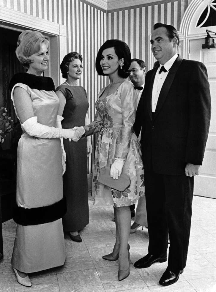 09/20/1965 - Isabell Gerhart welcomes guests, Cathy and Eddie Gilbert, to a black-tie party for New York couture designer Samuel Winston in her Kirby Drive home. Highlight of the evening for the 400 guests was a showing of Winston gowns.