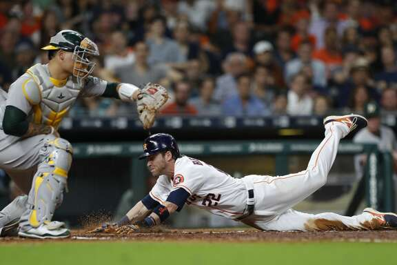 Houston Astros Josh Reddick (22) dives into home to score a run on a sacrifice fly by Brian McCann during the sixth inning of an MLB baseball game at Minute Maid Park, Wednesday, June, 28, 2017.  ( Karen Warren / Houston Chronicle )
