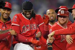 Los Angeles Angels' Cameron Maybin, center, celebrates with teammates after he made it to first on a overthrow error by Los Angeles Dodgers catcher Yasmani Grandal on a dropped strike three which allowed Ben Revere to score the winning run in the ninth inning of a baseball game, Wednesday, June 28, 2017, in Anaheim, Calif. (AP Photo/Mark J. Terrill)