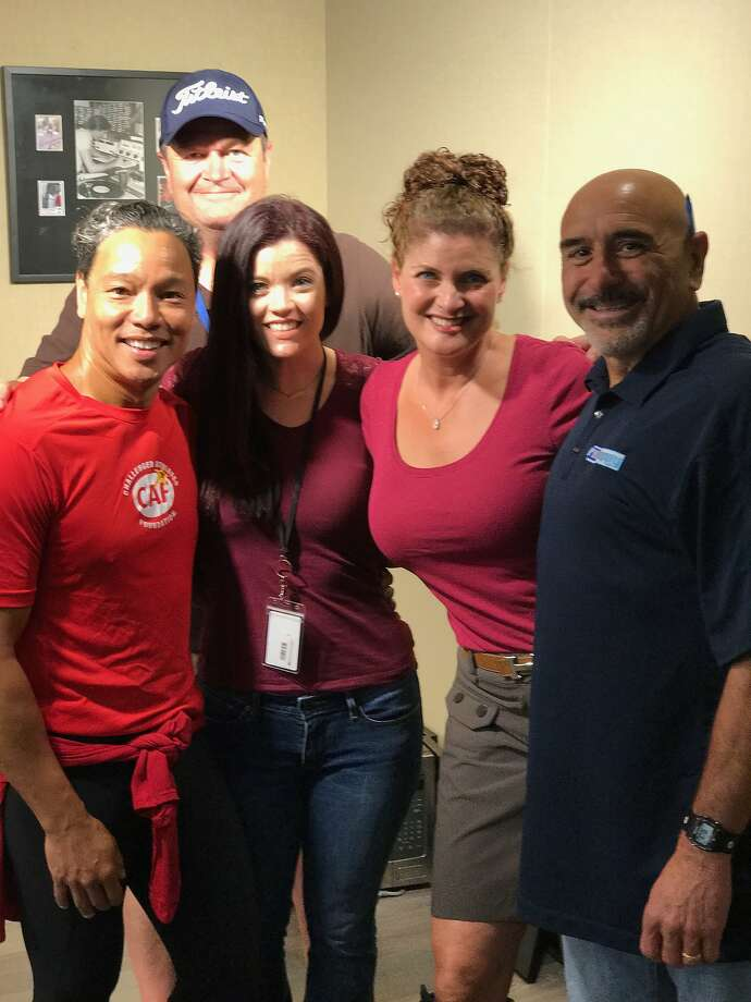 Paul Tonelli (right), back at work weeks after a heart attack, was recently joined in the studio by several of his lifesavers.