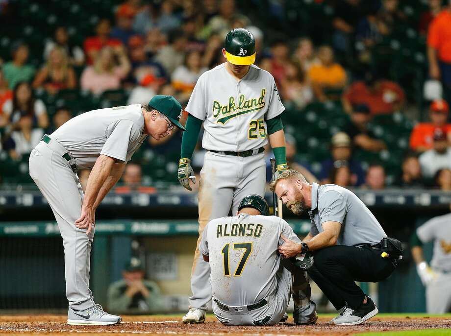 HOUSTON, TX - JUNE 28:  Yonder Alonso #17 of the Oakland Athletics is looked at by manager Bob Melvin #6 along with Ryon Healy #25 and the trainer after fouling a ball off his knee in the eighth inning against the Houston Astros at Minute Maid Park on June 28, 2017 in Houston, Texas.  (Photo by Bob Levey/Getty Images) Photo: Bob Levey, Getty Images
