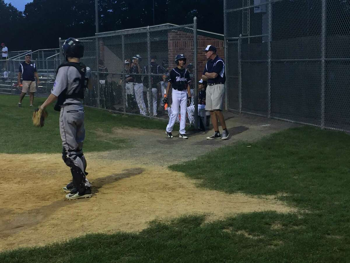 Westport coach Tom Whelan shares some wisdom with one of his players before an at-bat against Fairfield National on Wednesday evening at Unity Field in Trumbull.