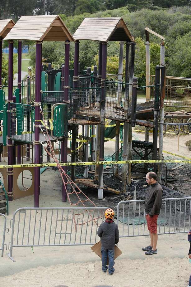 A father and son look at the play structure, apparently burned by vandalism, from the other side of a barricade. Photo: Lea Suzuki, The Chronicle