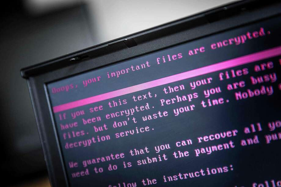 A laptop displays a message after being infected by a ransomware as part of a worldwide cyberattack on June 27, 2017 in Geldrop.  The unprecedented global ransomware cyberattack has hit more than 200,000 victims in more than 150 countries, Europol executive director Rob Wainwright said May 14, 2017. Britain's state-run National Health Service was affected by the attack. / AFP PHOTO / ANP / Rob Engelaar / Netherlands OUTROB ENGELAAR/AFP/Getty Images Photo: ROB ENGELAAR, Contributor / AFP/Getty Images / AFP or licensors