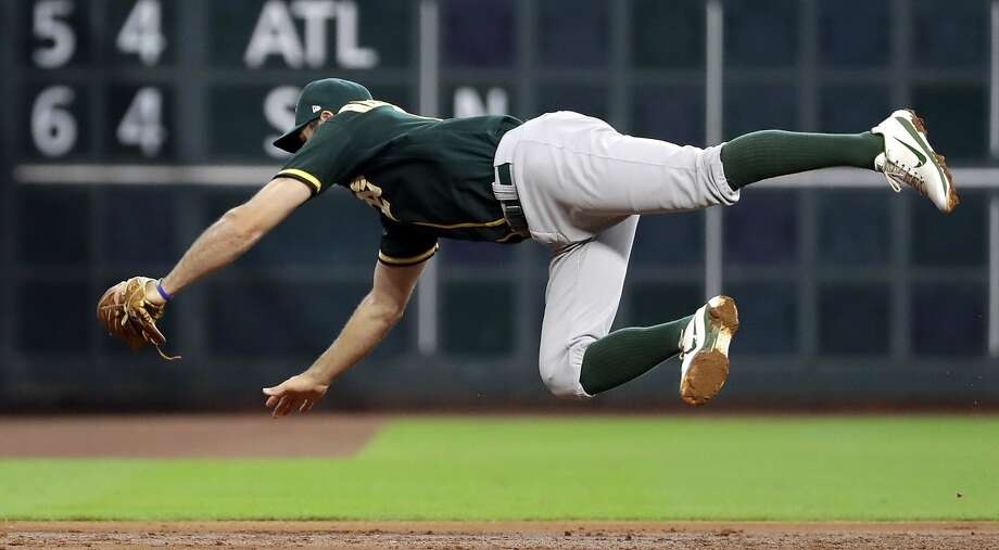 Oakland Athletics third baseman Adam Rosales makes a diving catch on a line drive by Houston Astros' Alex Bregman during the third inning of a baseball game Thursday, June 29, 2017, in Houston. (AP Photo/David J. Phillip) Photo: David J. Phillip, Associated Press