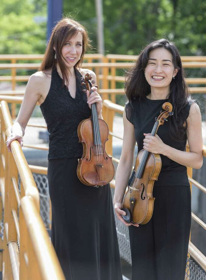 "Albany Symphony violinists Jamecyn Morey, left, and Mitsuko Suzuki pose at Erie Canal Lock E2 in Waterford. The Albany Symphony embarks Sunday, July 2, on its ""Water Music"" concert series traversing the canal. (Gary Gold Photography)"