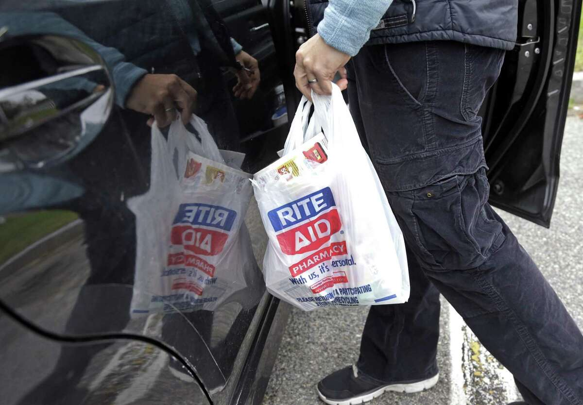 In this Wednesday, Sept. 28, 2016, photo, a shopper carries her purchases from Rite Aid into her car, in North Andover, Mass. Walgreens and Rite Aid will sell 865 stores to rival retailer Fred's for $950 million, possibly removing the final roadblock preventing the tie up between the nation's largest and third-largest drugstore chains, in news announced Tuesday, Dec. 20, 2016. (AP Photo/Elise Amendola)