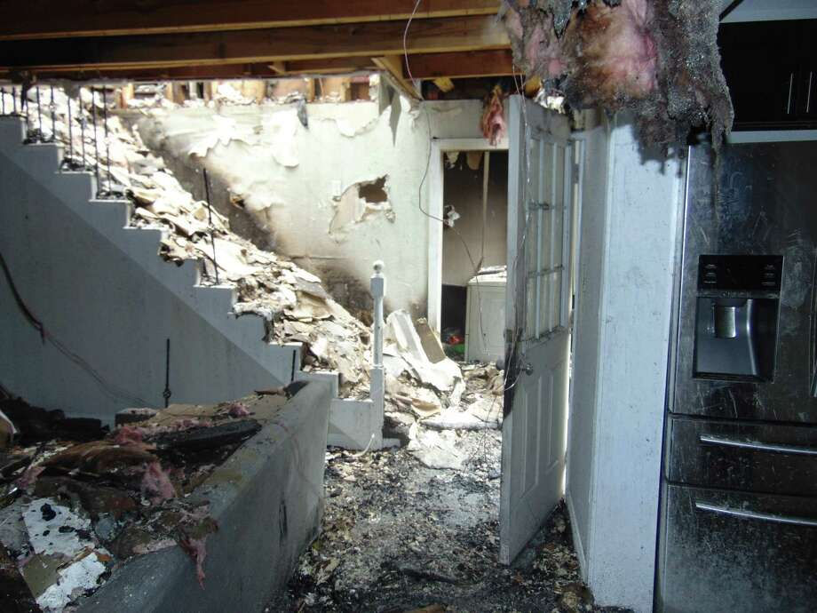 Two men are behind bars after authorities believe they intentionally set fire to their home near Magnolia earlier this month that injured a firefighter who fell through a hole in the second floor. Photo: Submitted Photo / Copyright 2009