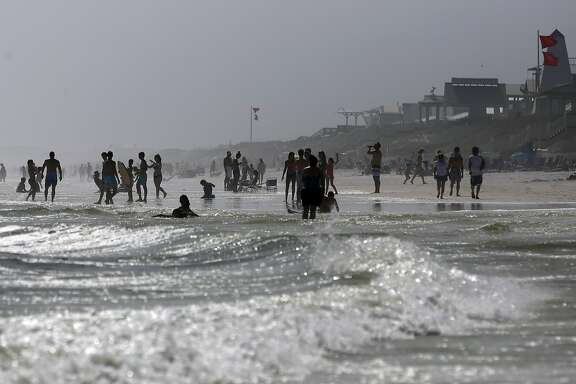FILE - In this June 22, 2017, file photo, beachgoers enter the water even though double-red flags are flying, warning of dangerous conditions and extremely rough surf in the remnants of Tropical Storm Cindy, in Seaside, Fla. An extensive first-of-its-kind study says global warming is likely to hit southern and poorer U.S. counties hard. The study released June 29, used more than 29,000 computer simulations to estimate different global warming scenarios that effect energy costs, agricultural production, deaths and other factors. (AP Photo/Kiichiro Sato, File)