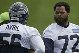 Seattle Seahawks defensive end Michael Bennett (72) talks with defensive end Cliff Avril, left, during NFL football practice, Tuesday, June 13, 2017, in Renton, Wash. (AP Photo/Ted S. Warren)