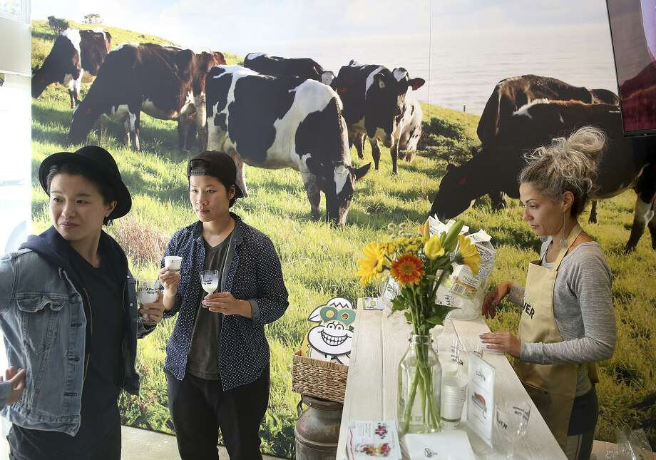 Food photographer Debbie Ma (left) and Beverly Nguyen (middle) visiting from Los Angeles taste milk at the Clover Milk Tasting Room pop-up in Hayes Valley on Wednesday. Clover Somoo'lier Bree Zimmerman is at right. Photo: Liz Hafalia / Liz Hafalia / The Chronicle / online_yes
