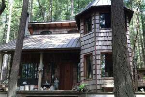 The first structure on the property is this log cabin home with a turret.