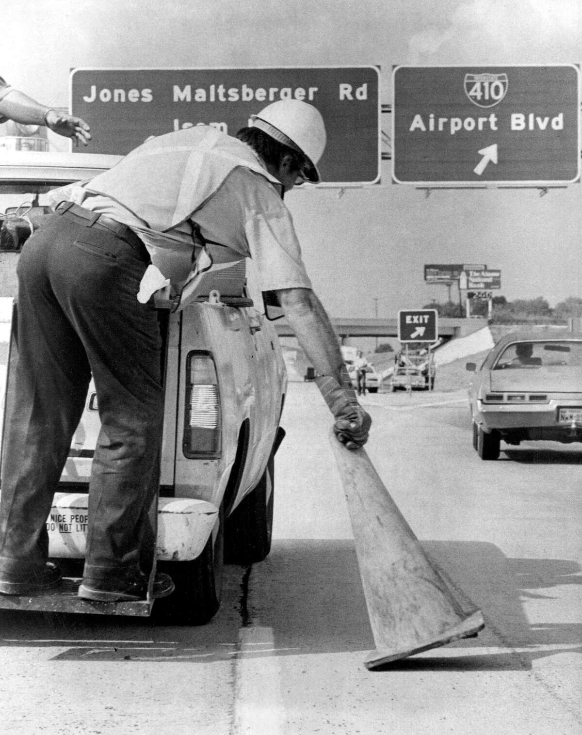 An employee of the state highway department picks up the last traffic cone to open McAllister Freeway, from downtown to San Antonio International Airport, in 1978. The freeway, also called U.S. 281 North, was extended to Loop 1604, and has been a major growth corridor for the city.