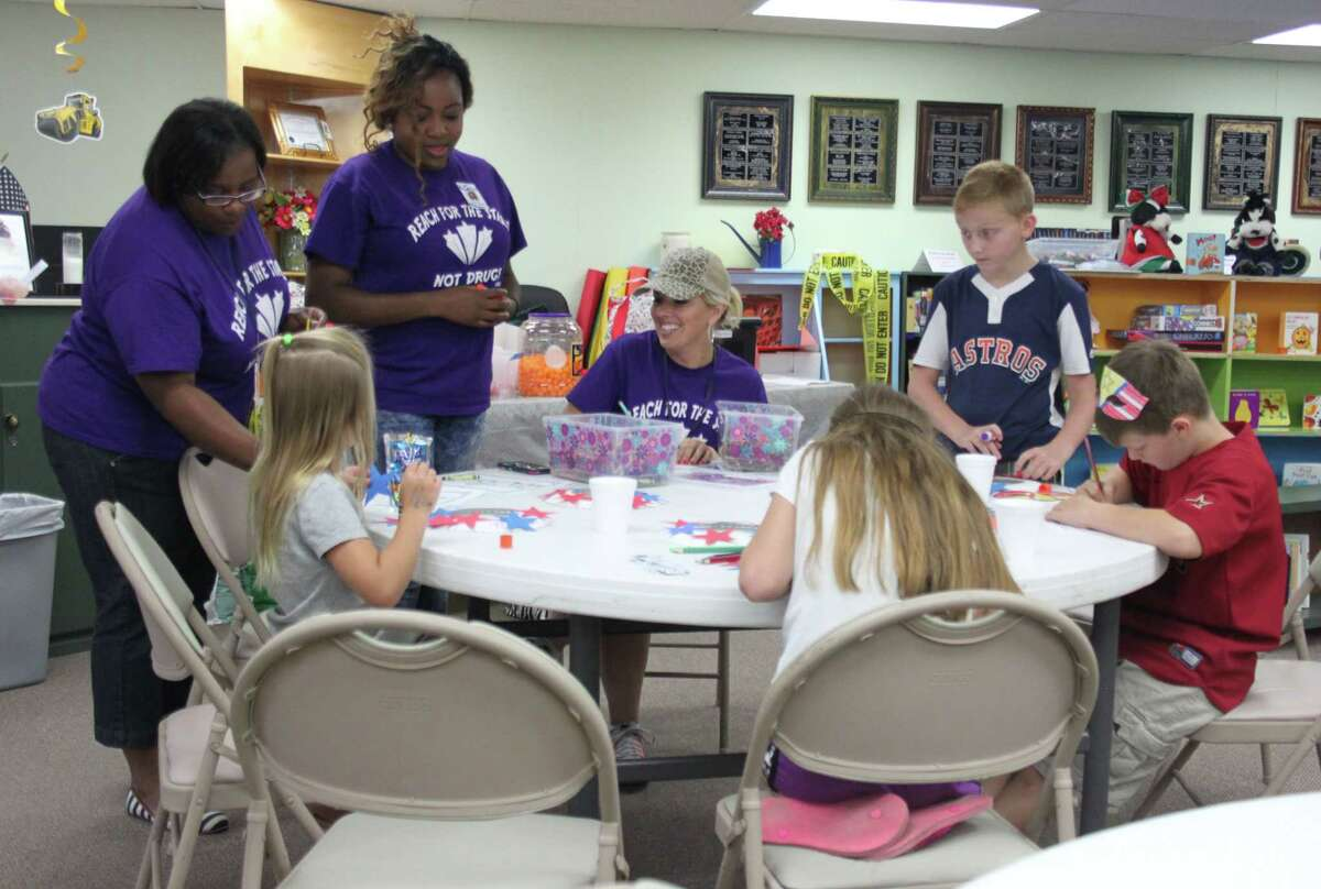 Members of the Alcohol and Drug Abuse Council teach children how to make patriotic wreaths during the Shepherd Public Library's Summer Reading program on June 28.