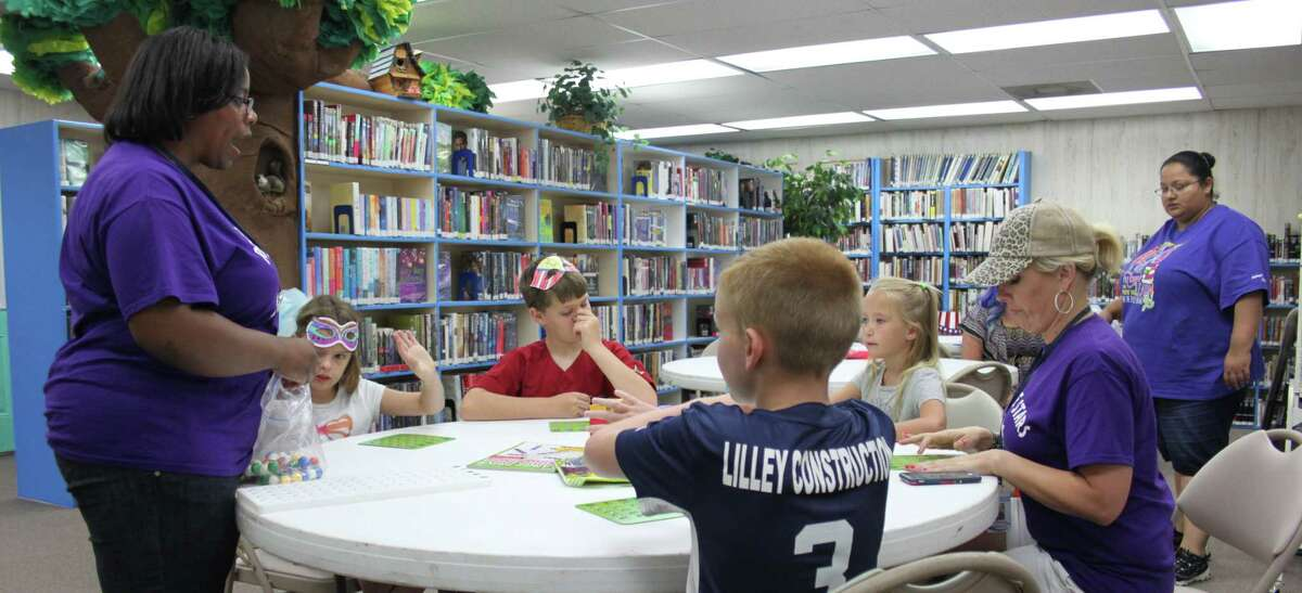 Shauna Kimbro (left) of the Alcohol and Drug Abuse Council starts a game of Bingo with children at the Shepherd Public Library's Summer Reading program.