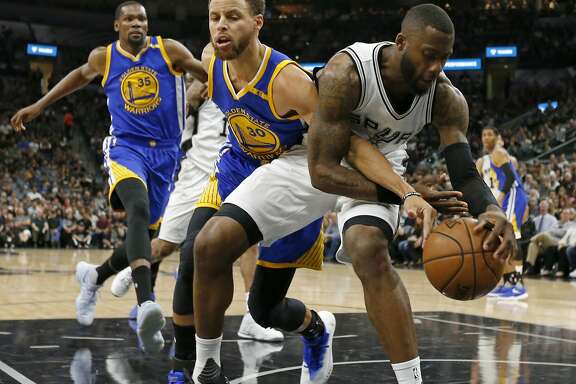 Golden State Warriors' Stephen Curry and San Antonio Spurs' Jonathon Simmons grab for a loose ball during first half action in Game 4 of the Western Conference Finals held Monday May 22, 2017 at the AT&T Center.