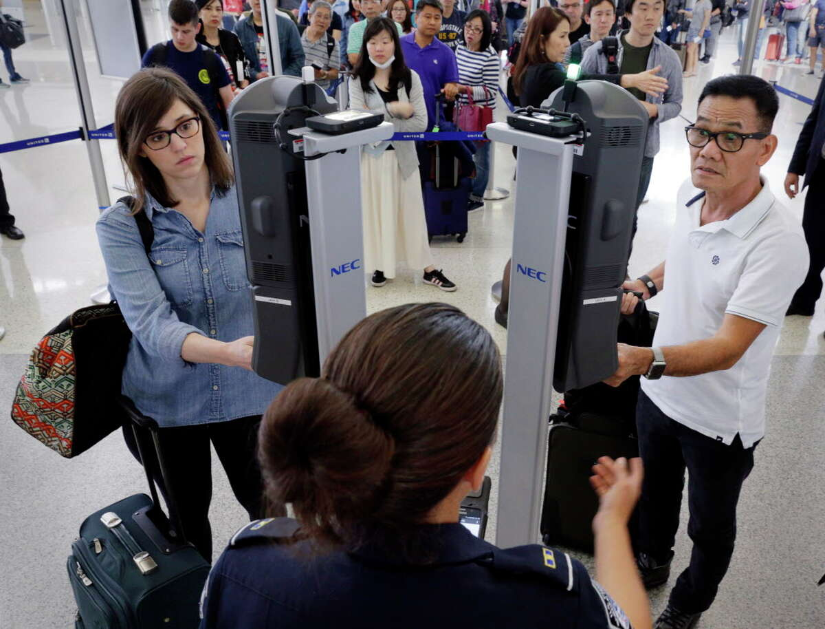U.S. Customs and Border Protection officer Charmaine Guillory (center bottom) stands by to assist passengers as they use the new face recognition kiosks being tested at United Airlines gate E7 before boarding a flight to Tokyo at Bush Intercontinental Airport in Houston, TX, June 29, 2017. When everything checks out, passengers spend less than 10 seconds at the kiosk before proceeding with the standard boarding activities. (Michael Wyke / For the Chronicle)