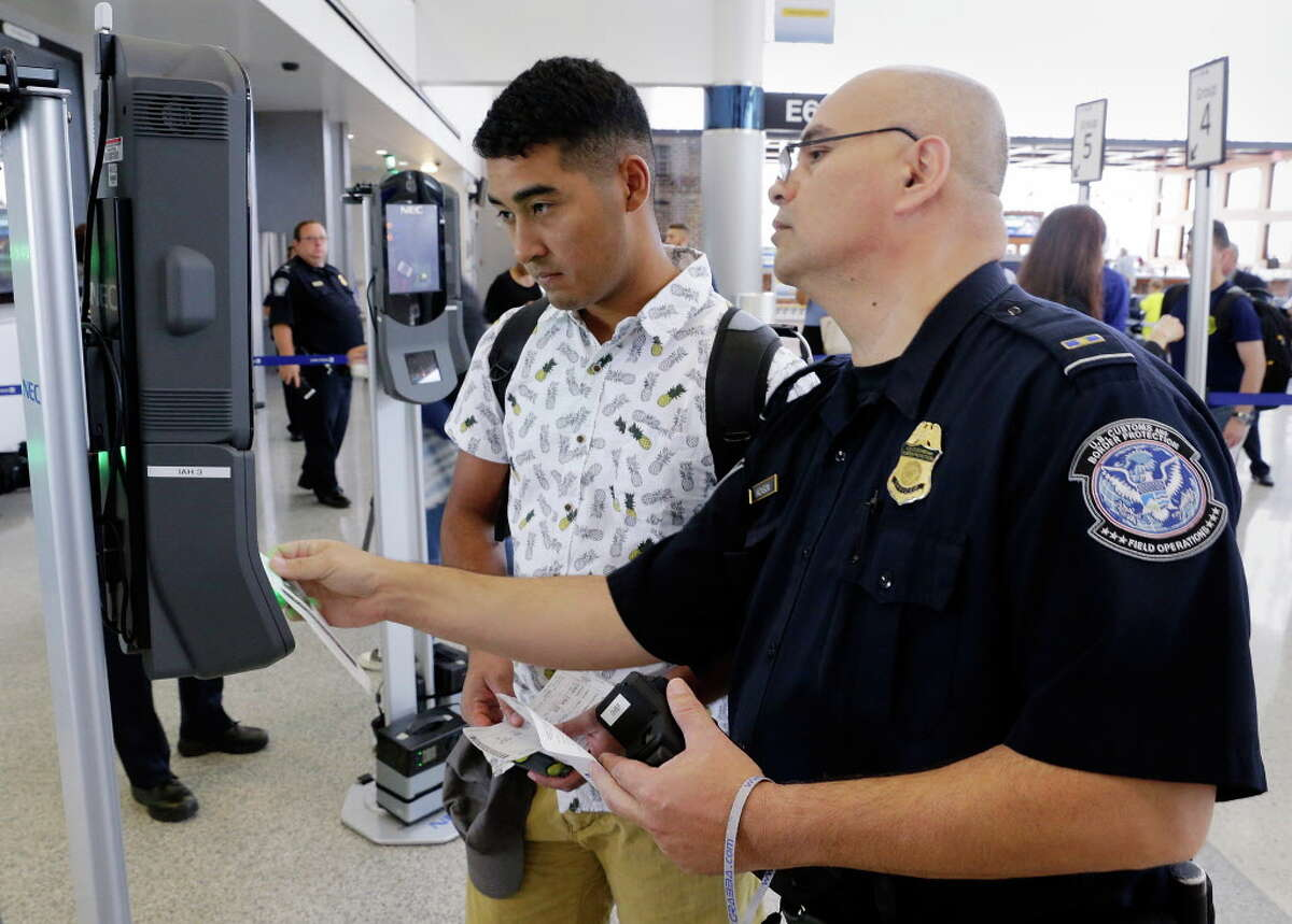 U.S. Customs and Border Protection officer Sanan Jackson (right) helps a passenger (no ID) navigate the new face recognition kiosks at United Airlines gate E7 for a flight to Tokyo at Bush Intercontinental Airport in Houston, TX, June 29, 2017. (Michael Wyke / For the Chronicle)