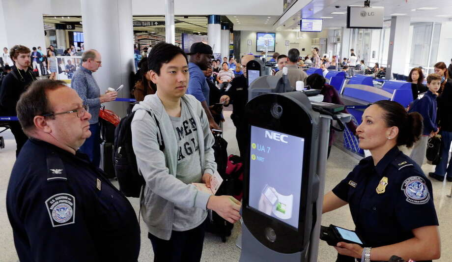 U.S. Customs and Border Protection chief watch commander Michael Entrekin (left) and officer Charmaine Guillory (right) assist passenger Vitalyi I (cq, center from Russia) as he uses the new face recognition kiosks being tested at United Airlines gate E7 before boarding a flight to Tokyo at Bush Intercontinental Airport in Houston, TX, June 29, 2017. When everything checks out, passengers spend less than 10 seconds at the kiosk before proceeding with the standard boarding activities. (Michael Wyke / For the  Chronicle) Photo: Michael Wyke, Freelance / © 2017 Houston Chronicle