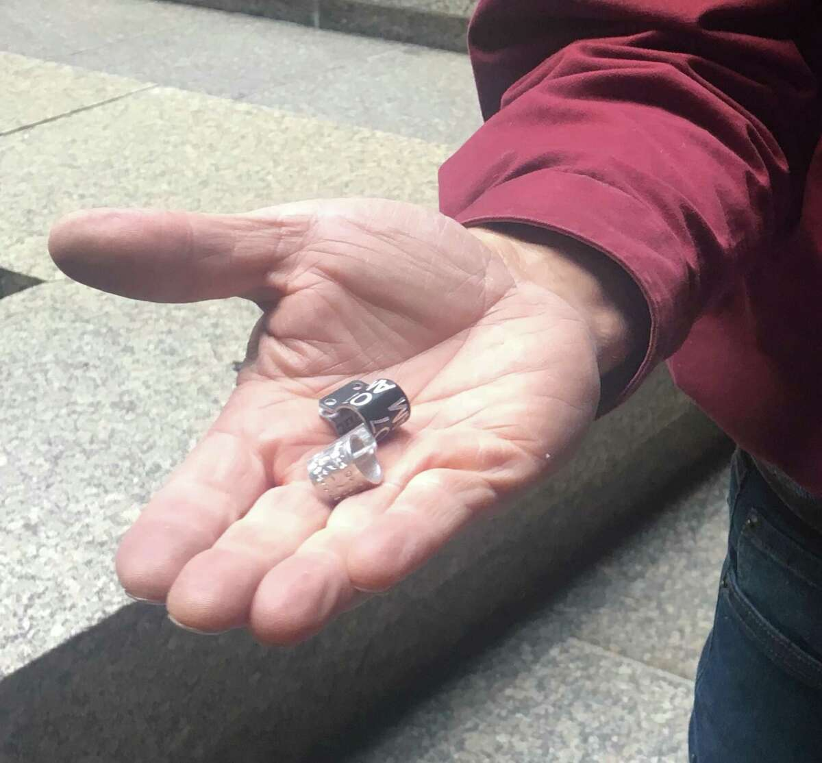 Glenn Stewart, director of the Predatory Bird Research Group at UC Santa Cruz, holds bands he placed on the legs of three peregrine falcons hatched earlier this month atop the PG&E building, 77 Beale St., in San Francisco.