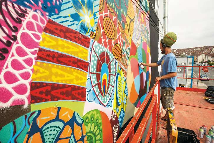 Artist Louis Masai works on a mural at the Redpoint Climbing Centre in Bristol, England.