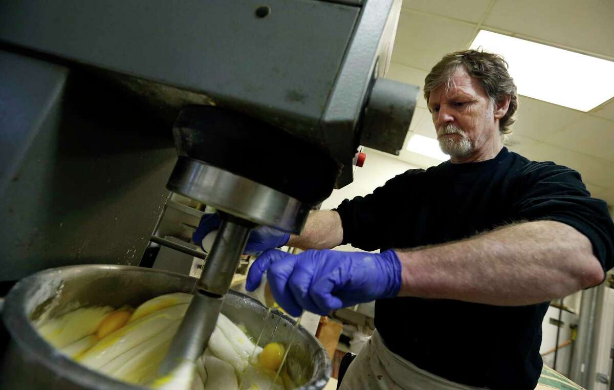FILE - In this March 10, 2014 file photo, Masterpiece Cakeshop owner Jack Phillips cracks eggs into a cake batter mixer inside his store in Lakewood, Colo.