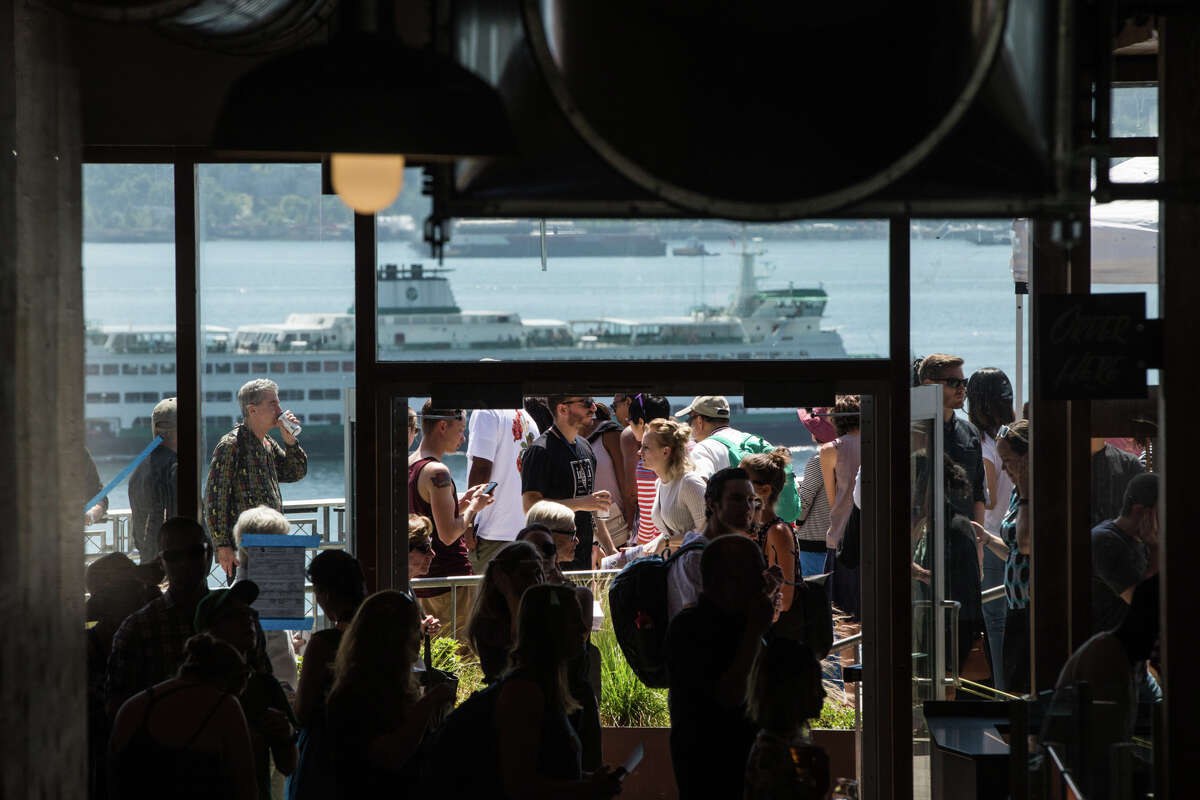 A ferry passes by as visitors explore the Producers Hall at Pike Place Marketfront's grand opening on Thursday, June 29, 2017.